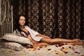 Yatakta yatıyordu çekici esmer — Stok fotoğraf