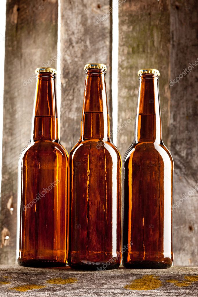 Three beer bottle on old wooden plank backbround — Foto Stock #11343645