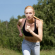 Beautiful young woman runner in nature — Stock Photo