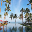 A Thai gulf, red umbrellas, plank beds and palm - Zdjęcie stockowe