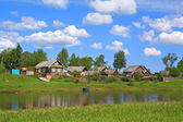 Aging village on river coast — Стоковое фото