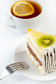 A cup of tea and a piece of tasty creamy cake with fruits — Stock Photo