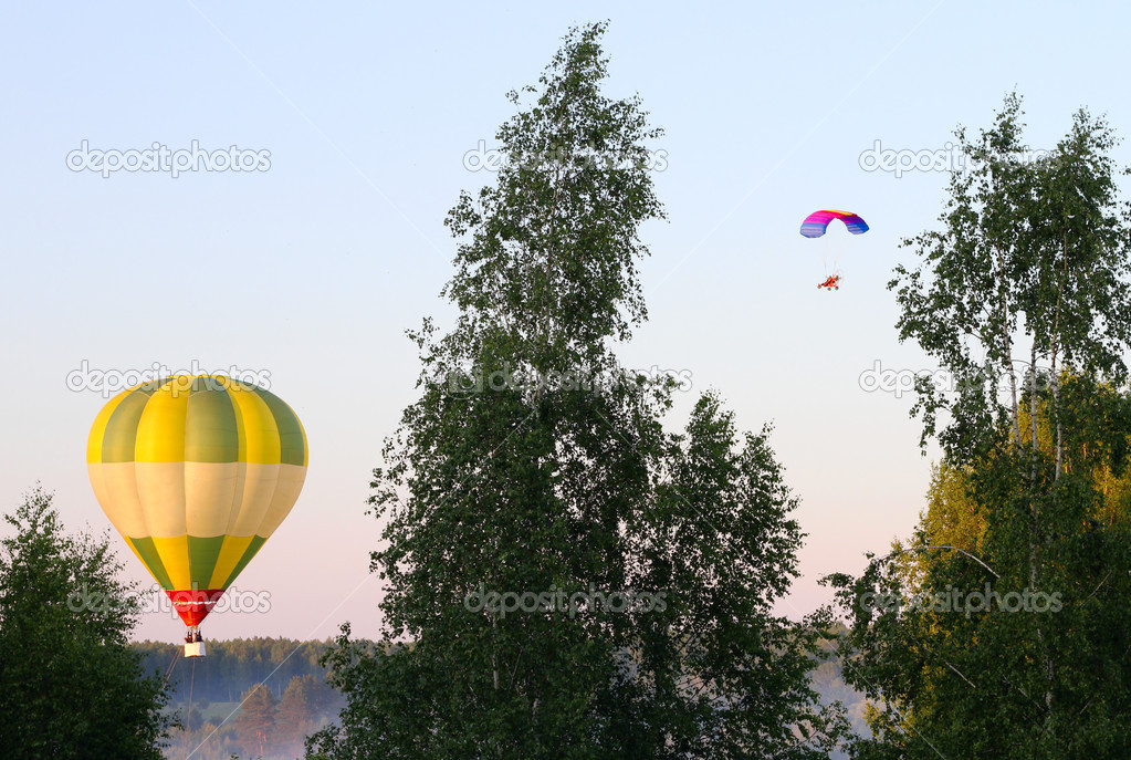 Air balloon and a paraglider above the forest — Stock Photo #10811559