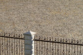 Old cobblestone paved yard behind the fence — Stock Photo