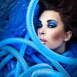 Futuristic beautiful young female face with blue fashion make-up. — Stock Photo