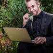 Young beautiful fashionable man with notebook against summer garden. - Stock Photo