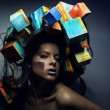 Fashion close-up portrait of beautiful young girl with cubes on head. Conceptual photo. — Stock Photo