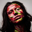 Close-up portrait of an artistic woman painted with red & green color. Part of face photo. — Stock Photo