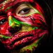 Close-up portrait of an artistic woman painted with red &amp;amp; green color. Part of face photo. - Zdjcie stockowe