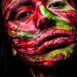 Close-up portrait of an artistic woman painted with red & green color. Part of face photo. - Stockfoto