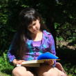 Stock Photo: Young girl doing homework outdoors