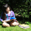 Young girl doing homework outdoors — Stock Photo