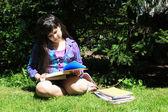 молодая девушка, делать домашнее задание на открытом воздухе — Стоковое фото