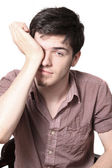 Tired male teen rubbing his eyes — Stock Photo