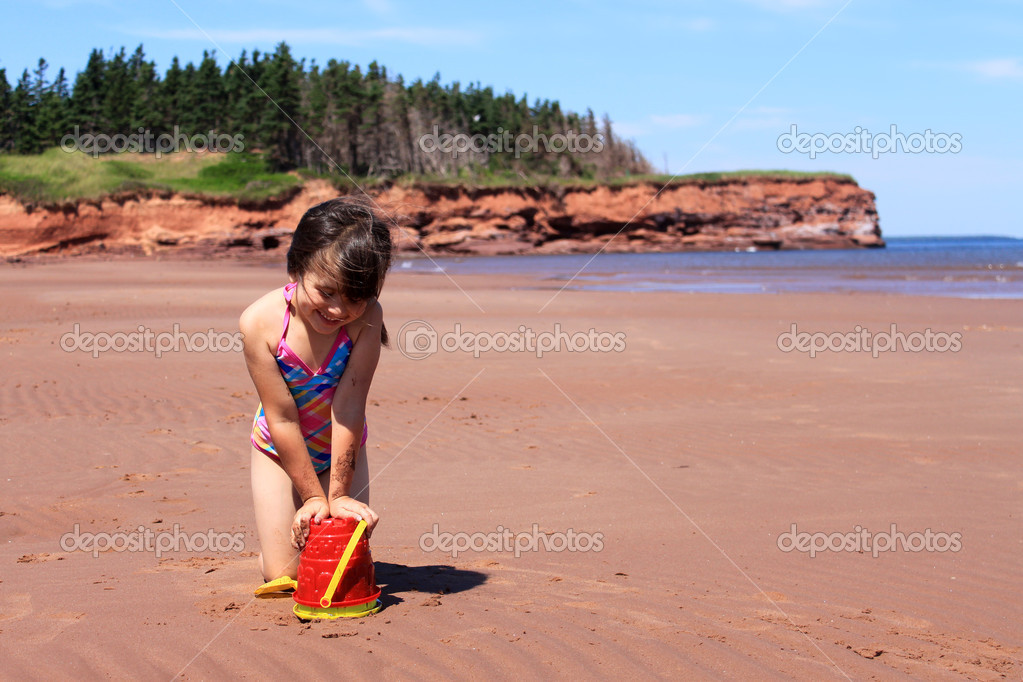 Llittle girl playing in the sand with toys at Cabot Beach, Prince Edward Island, Canada  Stock Photo #11707232