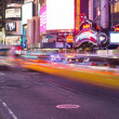 Stock Photo: NEW YORK - MARCH 7: Yellow cabs speed through Times Square landm