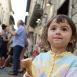 Stock Photo: Baby girl eating Ice Cream in the City Streets