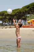 Bebé feliz lanzando la pelota en la playa — Foto de Stock