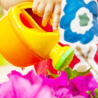 Child watering summer flowers — Stock Photo
