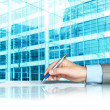 Businessman signing contract against modern offices — Stockfoto