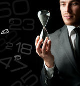 Businessman holding a hourglass — Stock Photo