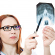 Female doctor examining X-ray image on a white background. - Stock Photo