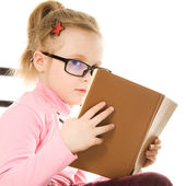 The little girl in glasses with a book — Stock Photo