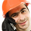 Male architect in a hardhat talks by a mobile phone — Stock Photo
