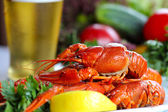 Heap of boiled crafish, glass of beer and garnish — Stock Photo