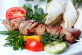 Shish pork kebab with greens and vegetables — Stock Photo