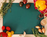 Vegetables still life with green board — Stock Photo