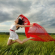 Brunette girl jumping with red fabric in summer day — Stock Photo