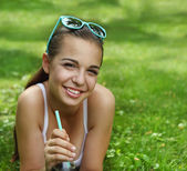 Beautiful young girl with lying on the grass — Stock Photo