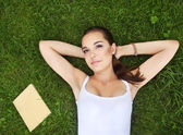 Beautiful young girl lying on the grass — Stock Photo