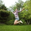 Brunette girl jumping in summer park — Stock Photo