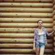 Stock Photo: Girl standing near wooden wall