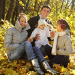 Family with two daughters in autumn forest — Stock Photo