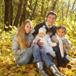 Family with two daughters in autumn forest — Stock Photo #11584209