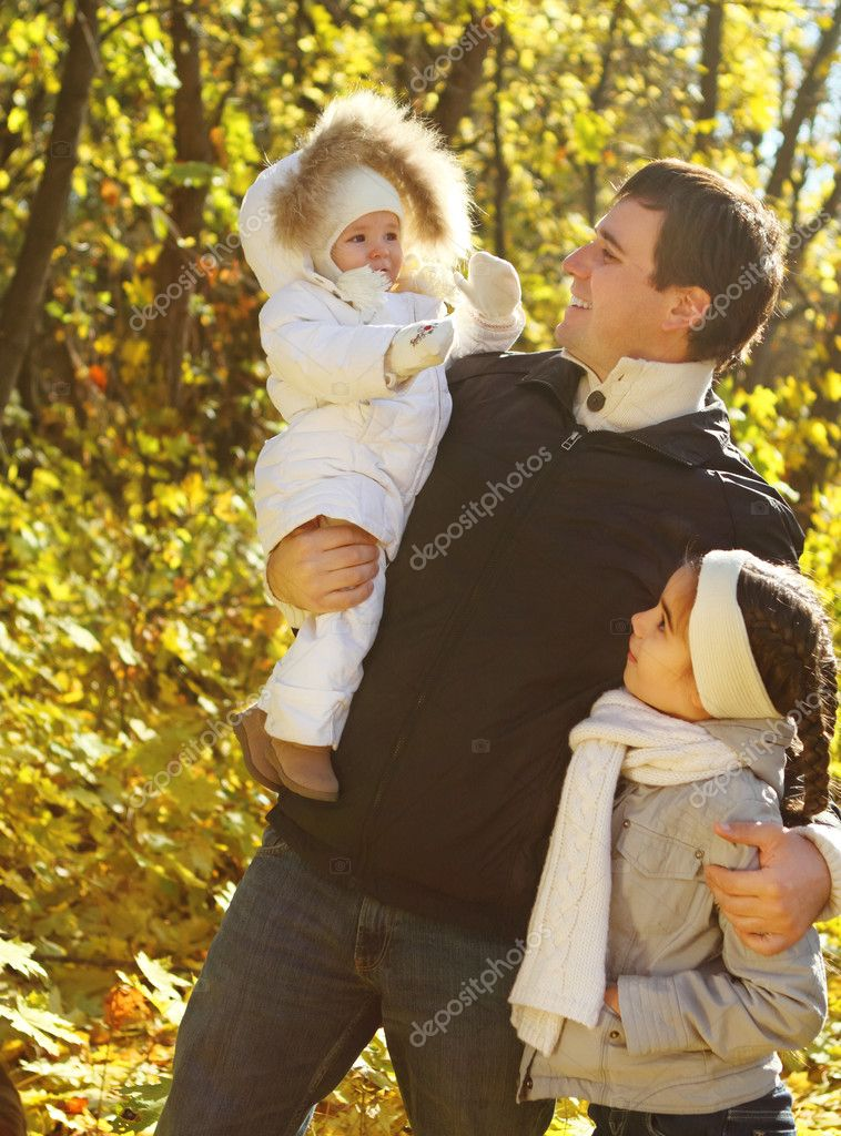 Young happy father with two daughters in autumn park — Stock Photo #11584212