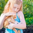 Little girl with cat outdoor — Stock Photo #11165140