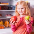 Girl with fruits on background refrigerator — Stock Photo #11165983