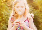 Little girl with dandelion outdoor — Stock Photo