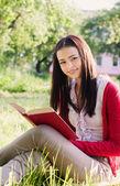 Belle fille lit livre dans un parc — Photo