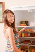 Beautiful girl on background refrigerator — Stock Photo