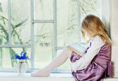Little girl reading book indoor — Stock Photo