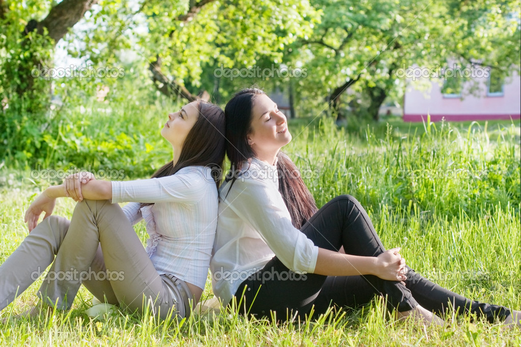 Two girls sitting down on green grass — Foto Stock #11161871
