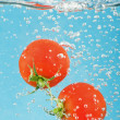 Bubbles forming in water after tomato are dropped — Stock Photo #11449477