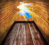 Hole in the brick wall of room with wooden floor — Stock Photo