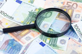 Magnifying glass lying on banknotes — Stock Photo