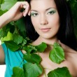 Beautiful woman with spring green leaves — Stock Photo